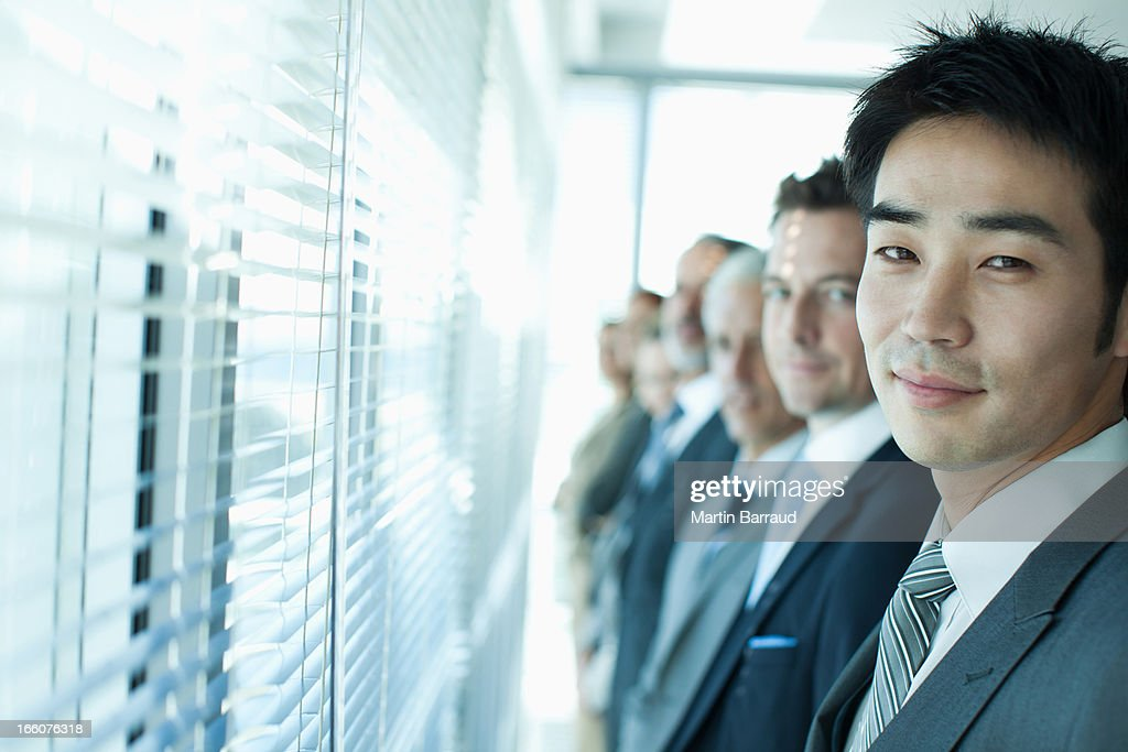Business people looking out window : Stock Photo