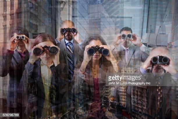 Business people looking through binoculars at office window