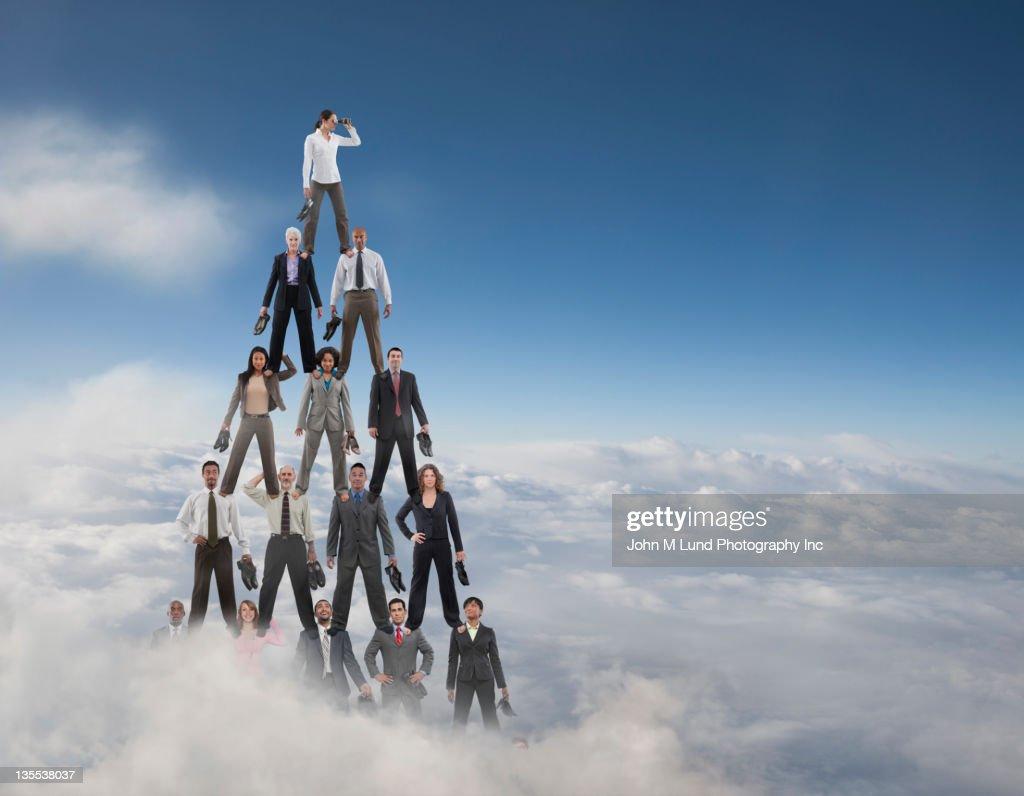 Business people making a human pyramid : Stock Photo