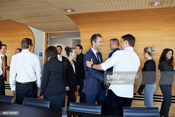 Business people making handshake in meeting room