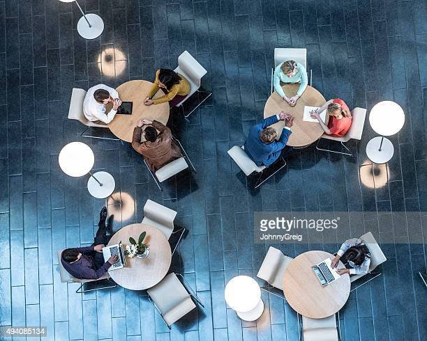 Business people meeting at tables, view from above