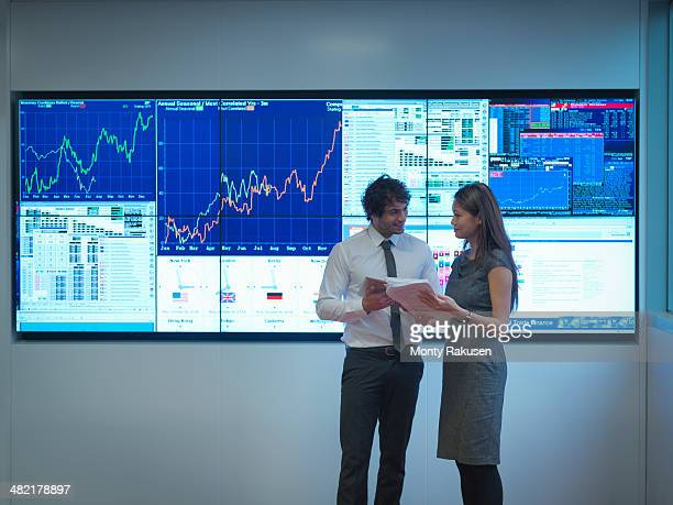 Business people meeting in front of graphical screens