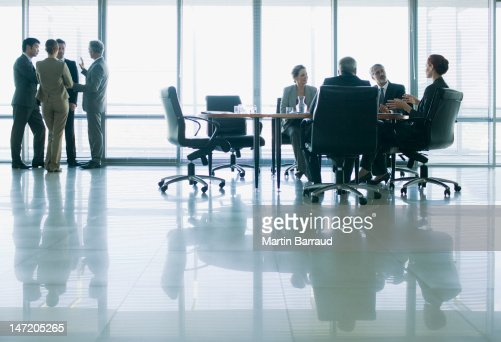 Business people meeting in separate groups in conference room : Stock Photo
