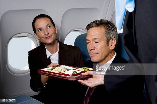 Business people on a plane being served airline food
