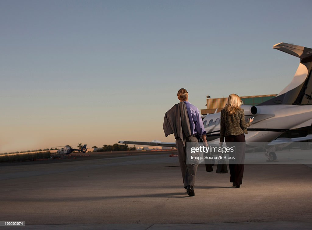 Business people on airplane runway : Stock Photo