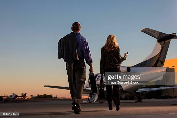 Business people on airplane runway