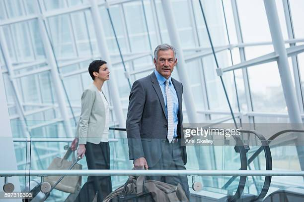 Business people on escalator in airport