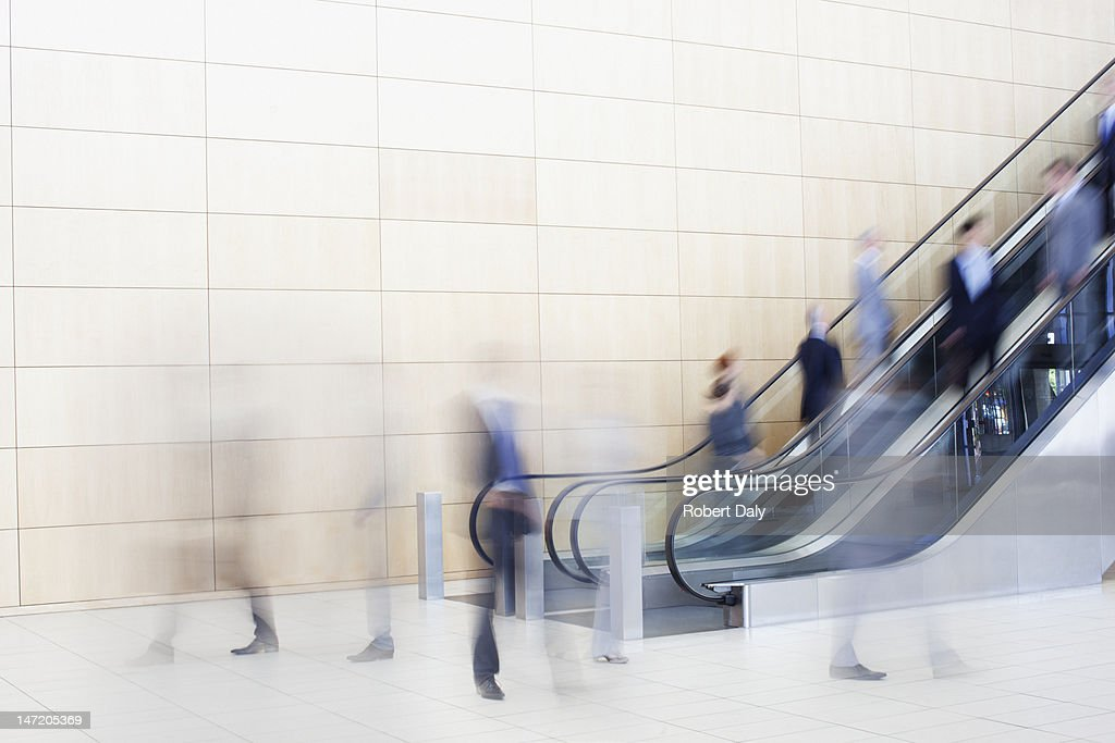 Business people on escalators