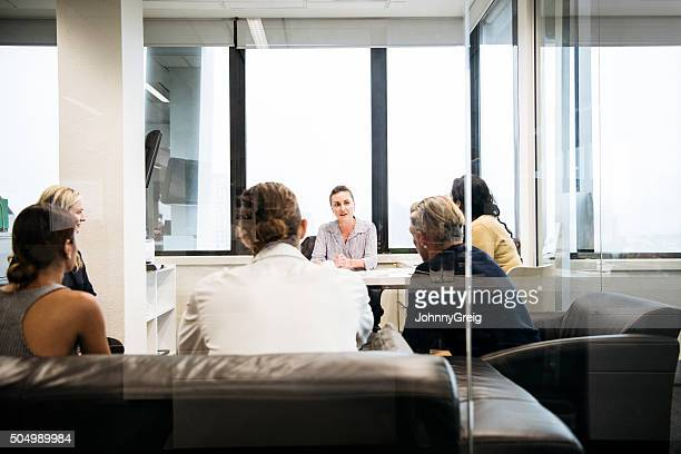 Business people on leather sofas meeting in modern office