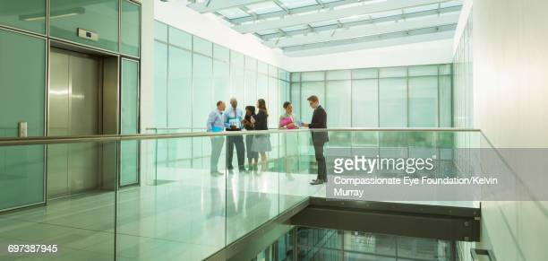 Business people on office atrium balcony