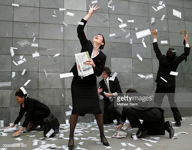 Business people on pavement catching falling money