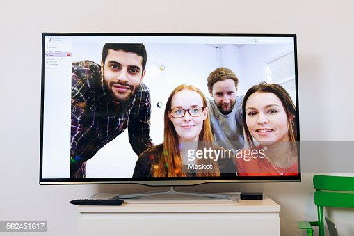 Business people on screen in video conference room at creative office