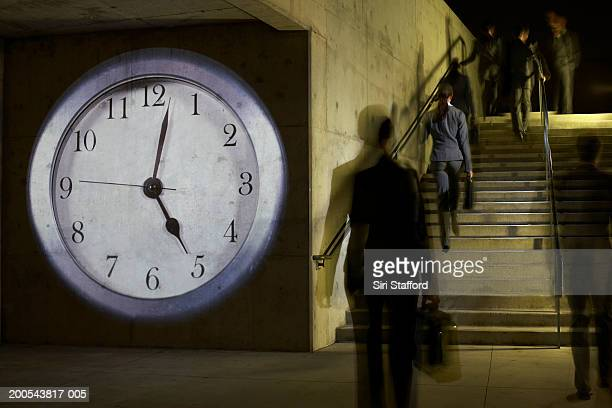 Business people on staircase, clock projected on wall