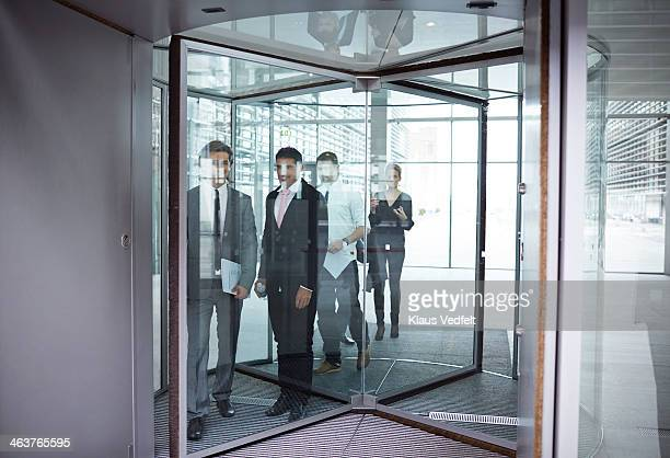 Business people on the way out of revolving door