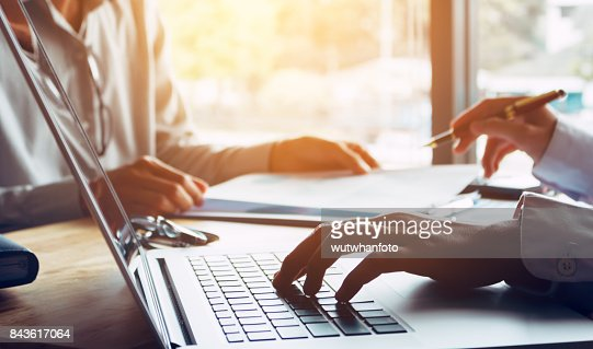 Business people or doctor talking to customer and using laptop at office room. : Stock Photo