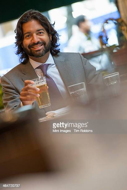 Business people out and about in the city. A Latino man seated at a table in a bar or cafe.