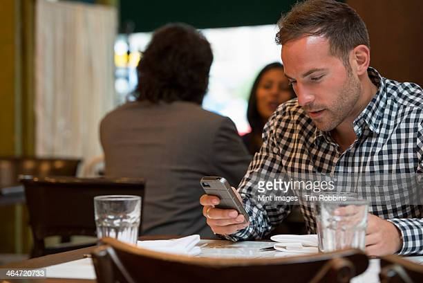 Business people out and about in the city. Two people talking to each other, and a man at a separate table checking his phone.