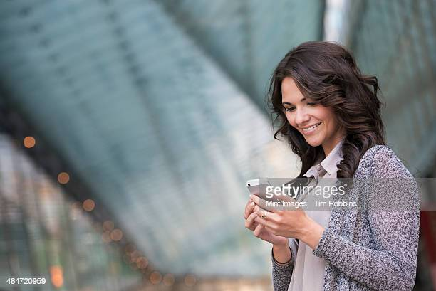 Business people outdoors, keeping in touch while on the go. A businesswoman in a light grey jacket, using her smart phone.