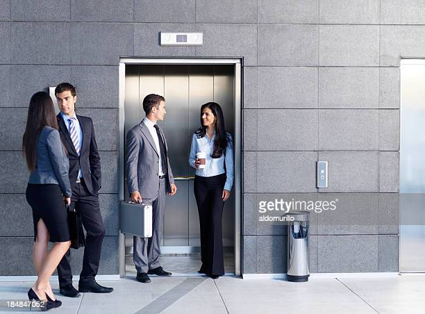 Business people outside the elevator