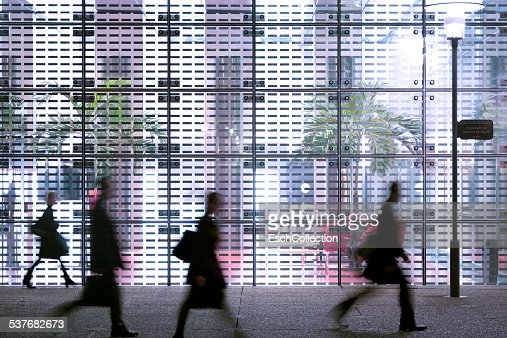 http://media.gettyimages.com/photos/business-people-passing-modern-office-building-picture-id537682673?s=170667a