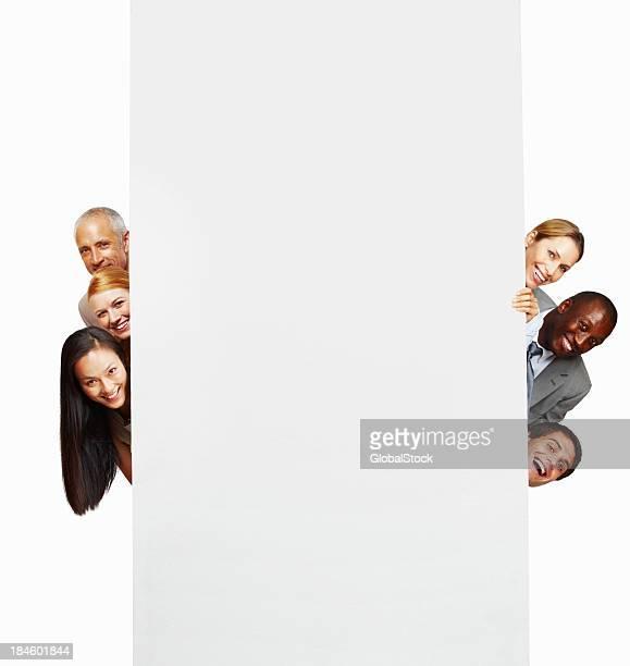 Business people peeking out behind blank board