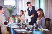 Business people placing an order with waiter at hotel restaurant