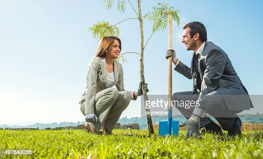 Business people planting tree and communicating.