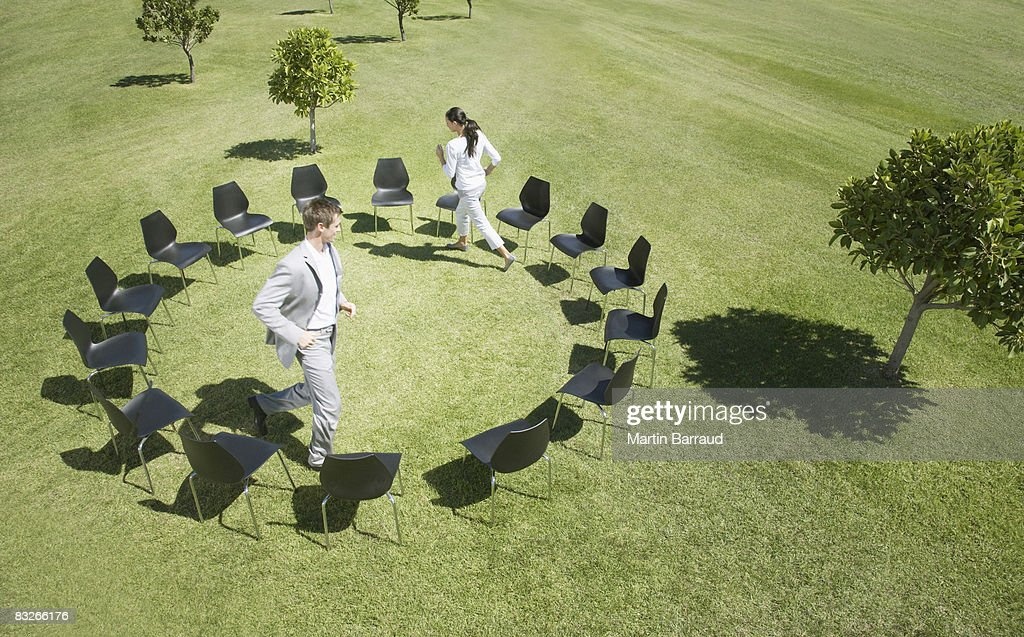 Business people playing musical chairs in field : Stock Photo