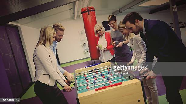 business people playing table soccer