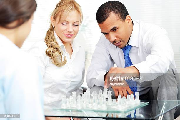 Business people playing the chess.