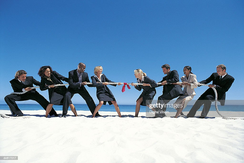 Business People Playing Tug-of-War on the Beach