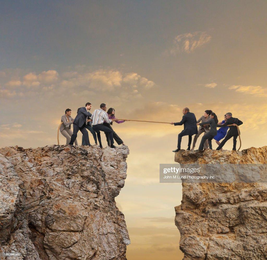 Business people playing tug-of-war over canyon