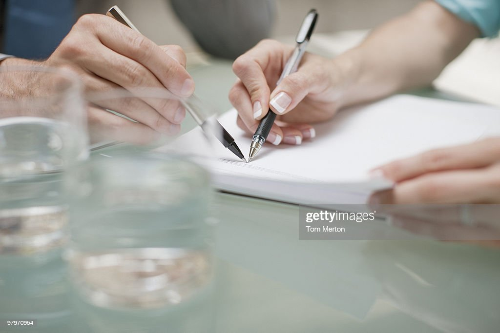 Business people pointing at paperwork with pens