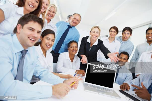 Business people presenting a blank laptop screen
