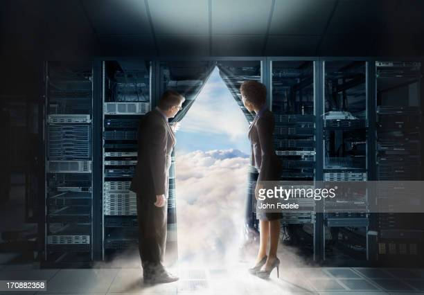 Business people pulling back curtain to clouds