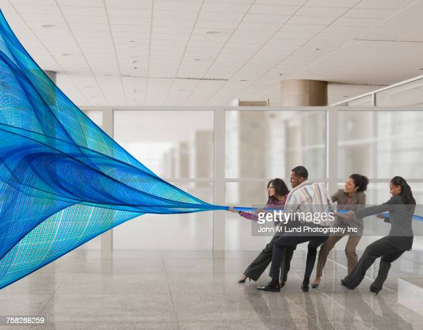 Business people pulling blue waves of information