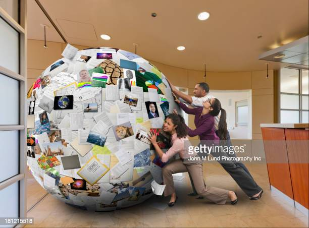 Business people pushing globe of images