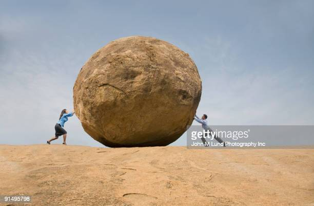 Business people pushing large rock against each other