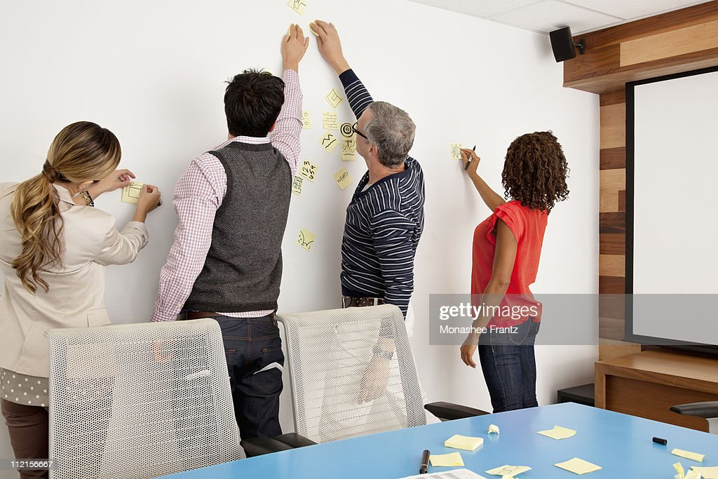 Business people putting adhesive notes on conference room wall : Stock Photo