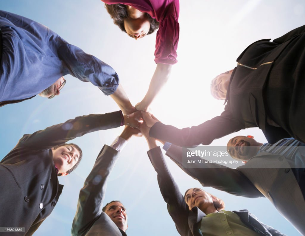 Business people putting hands together outdoors : Stock Photo