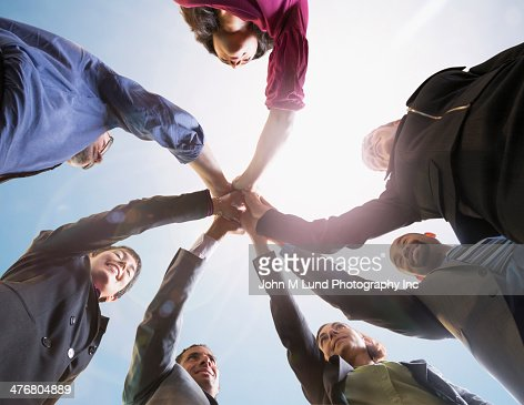 Business people putting hands together outdoors