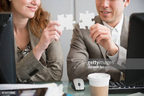 Business people putting puzzle pieces together at desk