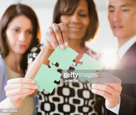 Business people putting together green puzzle : Stock Photo