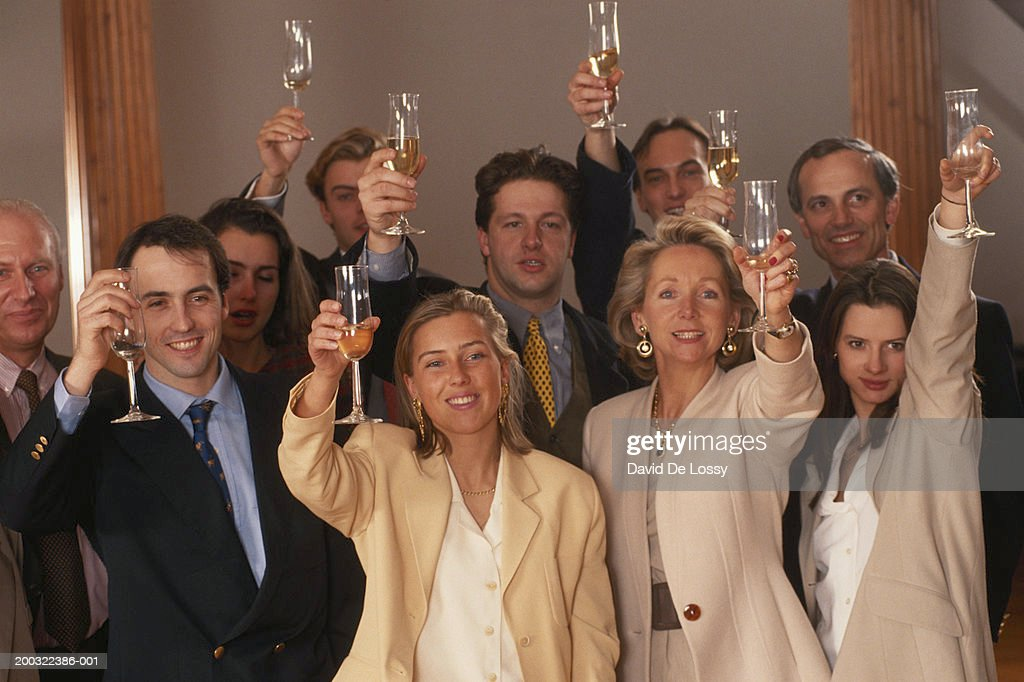 Business people raising glasses in office, smiling : Stock Photo