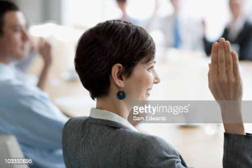 Business people raising hands in meeting in conference room : Stock Photo
