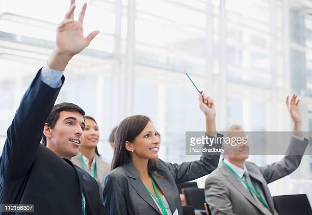 Business people raising hands in seminar
