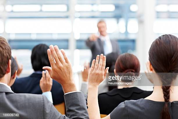 Business People Raising Their Hands at a Conference