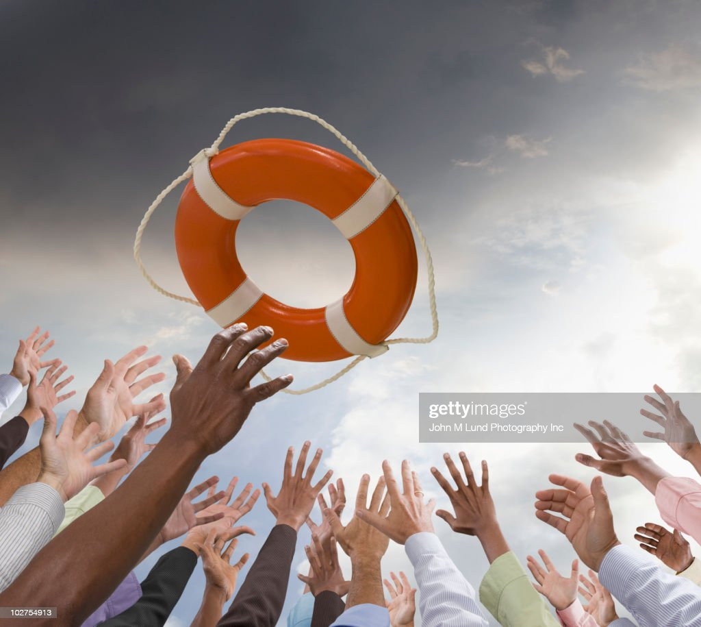 Business people reaching for life preserver
