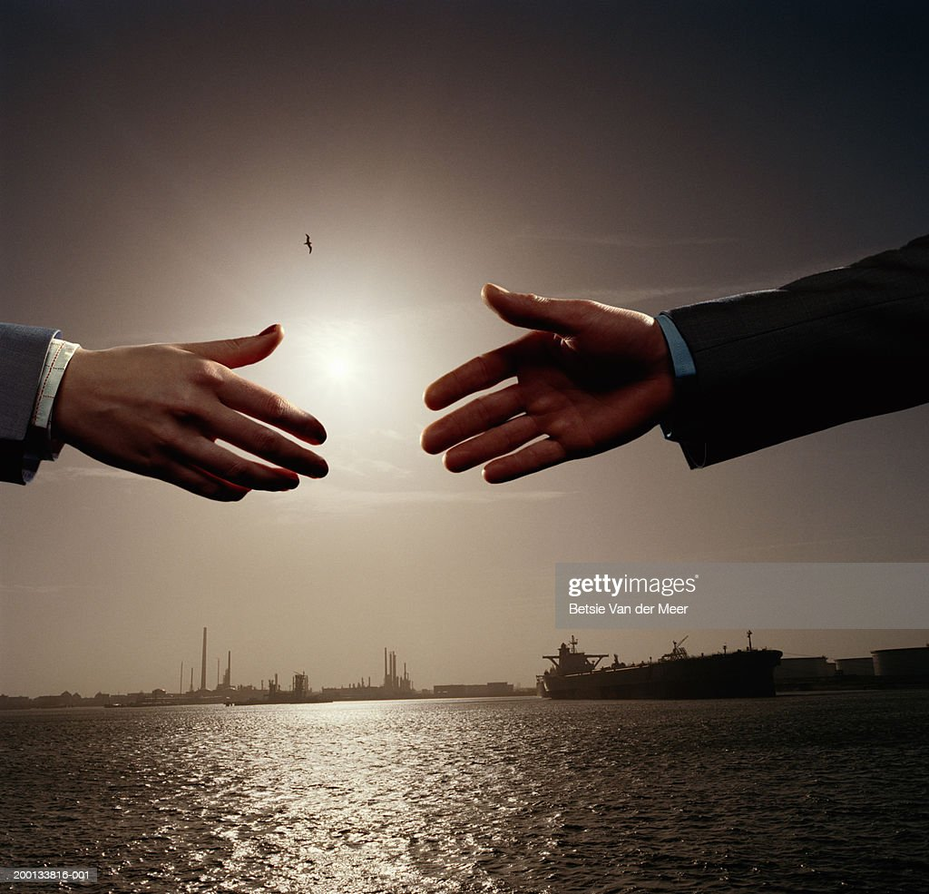 Business people reaching to shake hands outdoors (Digital Composite) : Stock Photo