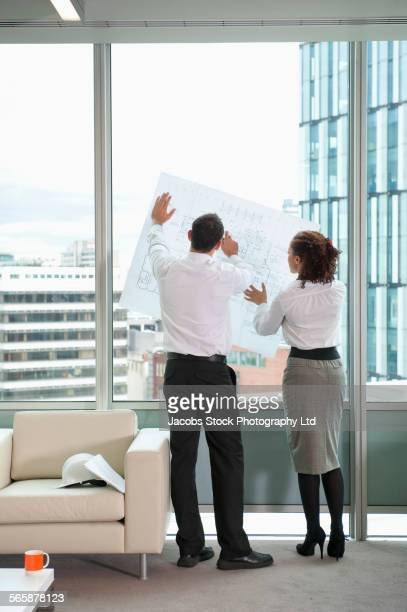Business people reading blueprints at office window